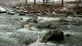 Rushing stream crashes over snow-covered boulders  24441154