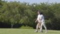 爽やかな緑の公園を、腕を組み散歩するシニア夫婦 25572251