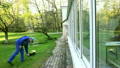Man washing conservatory window with water jet 25977416