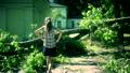 Worried woman climbing over fallen tree on house 26013933