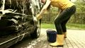 Girl washing automobile in open air. Handheld shot 26101674