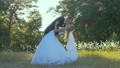 Happy groom holds in arms and kisses his bride 26137415