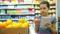 little girl holds a tablet at the store market 26282203