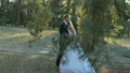 Groom embraces the bride in a park in the sunshine 26949957
