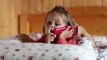 Funny little girl with red smartphone lies on bed 28308898