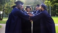 happy students in mortar boards with hands on top 28537733