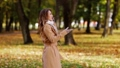 woman with smartphone walking in autumn park 28537893