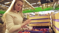 Young girl chooses red apples in supermarket stock 28987991