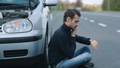Man siitting near broken car and calling for help 29130902