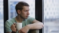 Relaxed young hipster drinking coffee near window 29632421