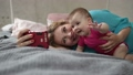 Mother and baby taking selfie with phone in bed 31006366