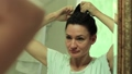 Woman looks into the mirror and makes a hairdo 31297031