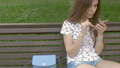 Young beautiful girl is sitting on a park bench 31626473