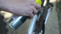 Cyclist with oil spray lubricates bicycle chain 32285068