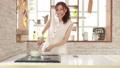 お洒落なキッチンでスマホ見ながら料理する女性 32445227