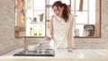 お洒落なキッチンでスマホ見て料理する女性 32445232
