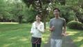 ファミリーイメージ 若い夫婦 新緑の中をウオーキングする スローモーション 32486054
