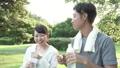 ファミリーイメージ 若い夫婦 新緑の中で水を飲む スローモーション 32486157