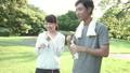 ファミリーイメージ 若い夫婦 新緑の中で水を飲む スローモーション 32486158