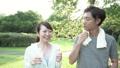 ファミリーイメージ 若い夫婦 新緑の中で水を飲む スローモーション 32486159