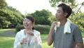 ファミリーイメージ 若い夫婦 新緑の中で水を飲む スローモーション 32486161