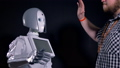 A technician slaps female robots hand. 32644476