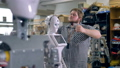 An engineer removes screws holding robots head 32916689
