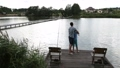 Father and son angling at tranquil lake in summer 33016537