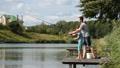 Dad and teenage boy angling together on lake 33016544