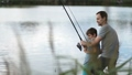 Excited father and son pulling fish out from lake 33016551