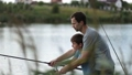Smiling dad and son fishing and relaxing at pond 33016571