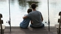 Affectionate father embracing son as they fish 33016576