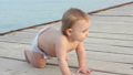 Smiling baby creeps on the pier in the diaper 33584327