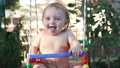 Smiling baby riding on a swing and laughing 33584329