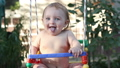 Smiling baby riding on a swing and laughing 33584330
