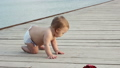 Smiling baby creeps on the pier in the diaper 33584332