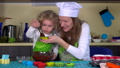Mom and daughter three years pour batter into cup 33896573
