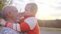 Grandson in his grandfather's arms at sunset 35024823