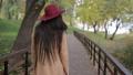 Trendy woman walking on wooden bridge in park 35352661