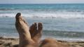 Legs of Men Lying on Beach near the Sea, POV. Slow 35963222