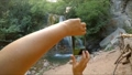 Hands make a photo of a waterfall on the phone. 37499345
