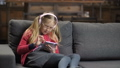 Cute girl in headphones using touchpad on sofa 37737599
