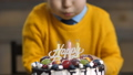 Midsection of toddler boy blowing candles on cake 37737600