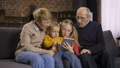 Family using tablet pc on sofa together at home 37737630