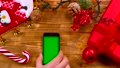 Man's hand puts the phone on the table, toys lie 37779354