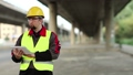 Workman with tablet computer under overpass 38463089