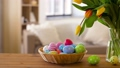 colored easter eggs in basket and flowers at home 39951841