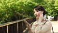 ผู้หญิงฟังเพลงจากสมาร์ทโฟนกลางแจ้ง 40124497