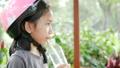 Asian little girl wearing pink helmet drinking wat 40296780
