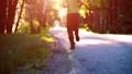 Sport man running at asphalt road. Rural city park. Green tree forest and sun rays on horizon. 40501930